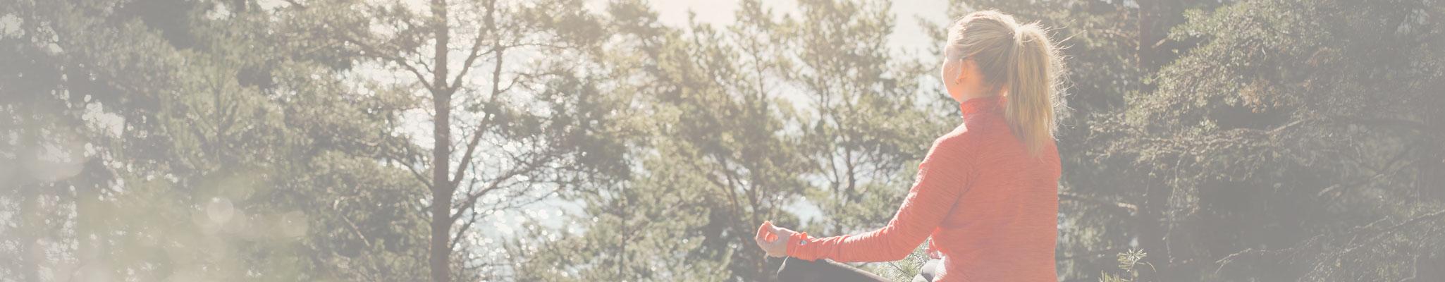Kvinna mediterar och yogar i naturen utanfor VANN Spa